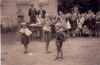 """W scence przedstawionej na zdjęciu, chłopiec z tornistrem na plecach – to mój brat Eugeniusz (kandydat na ucznia """"pierwszaka""""). Wśród """"widzów"""" jest też siostra Alicja (stoi w drugim rzędzie z białą wyróżniającą się kokardą ), a obok w pobliżu stoi p. Ostrycharczyk."""